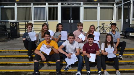 Clevedon School pupils sit on the steps of their school with their results. Picture: Eleanor Young