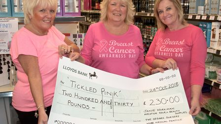Julie Sketchley (left) presenting cheque to sister Janie Workman (centre) with friend Julie Yianni (