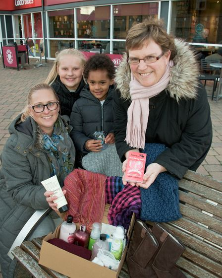 Steph Opogah and her children, Alexandra and Mikey, and Jill Bromley with some items in a box. Pi
