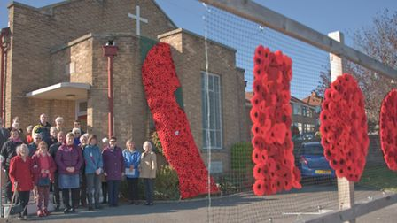 Worshipers outside Milton Methodist church with their knitted poppy cascade. Picture: MARK ATHERT