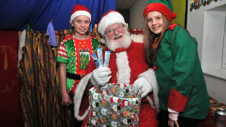 Elves Emily 10 and Evie 10 with Santa at St Andrew's Primary School. Picture: Jeremy Long