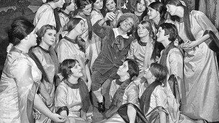 "Reginald Bunthorne (Geoffrey Blackmore) considers the lily surrounded by ""twenty love-sick maidens,"""