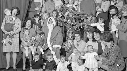 Infants and parents with Father Christmas around the tree at the party held at Bleadon Infant Welfar
