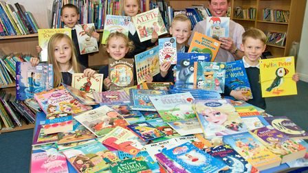 Asst. headteacher Chris Jones and pupils from Mary Elton Primary School, with over 100 books from th