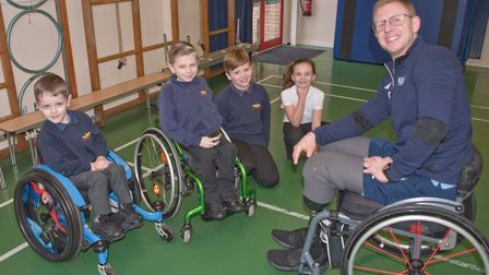 Aaron Phipps, part of the Team GB wheelchair rugby team, talking with pupils Jacob, Ashton, Harrison