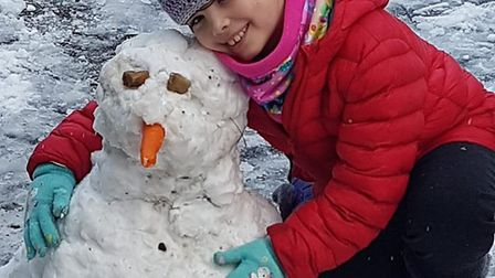 Clare Sampson's saughter Phoebe with a snowman. Picture: Clare Sampson