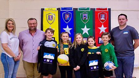 The two business directors with pupils from the school's football and netball teams.