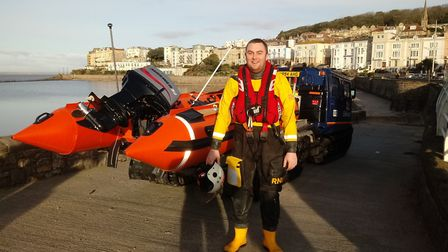 New Weston-super-Mare RNLI boat crew member Matt Lyons stood in front of the D Class Adrian Beaumont