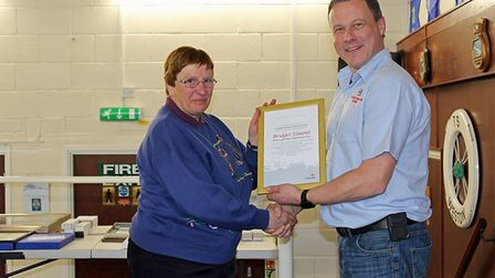 Weston RNLI Lifeboat Operations Manager Mike Buckland presenting an award to Birdget Elmont, shop ma