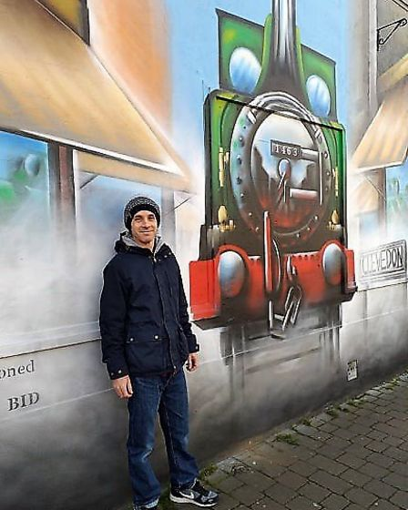 Damien Jeffery with his train mural on Station Road. Picture: Julie Bisacre