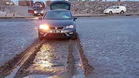 The rescue team waited for the tide to recede before pulling the car to safety.