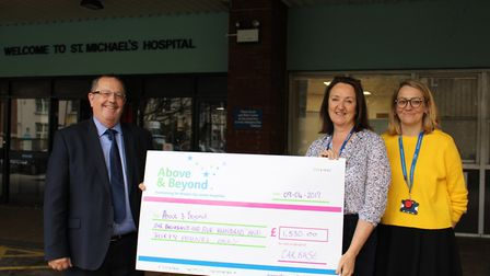 Gordon Veale handing over the donation to Rebecca Morgan and Gemma Jenkins.