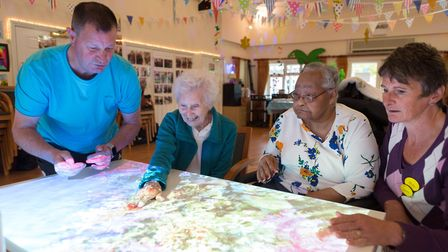 Wayne Lawn and Jacky Seymour using the magic table with residents at The Russets.