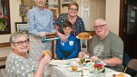Sheila Bond and Kath Kidd with Toby serving tea and cakes to Barry and Janette Millard at All Things