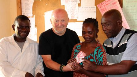 Paul Temple stood beside residents of Luhimba, Africa.