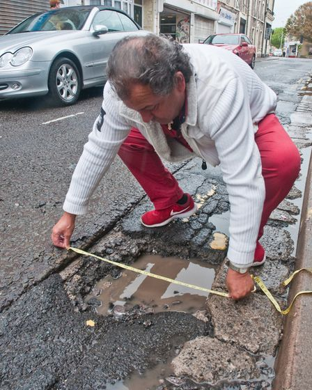 George Lati showing the size of the pot hole. Picture: MARK ATHERTON