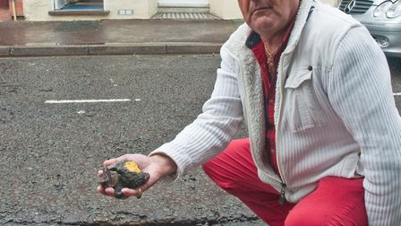 George Lati showing the stones that come out of the pothole. Picture: MARK ATHERTON