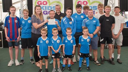 Priory Pumas receiving their cheque from Ellie Young and MC Tim Lamb at Weston Lions Club Go Kids Go