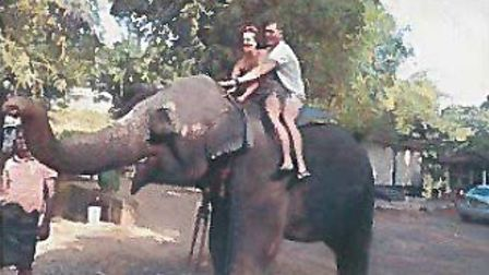 Natalie Davis on an elephant with her partner, Karl Simpson, in East Asia in 2015. Picture: DWP
