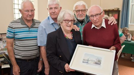 Pat Hase (centre) receiving at painting from Arthur Spencer watched by John Montacute, Weston U3A ch