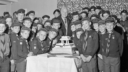 An iced, two-tier cake was cut by the County Commissioner of the Scout movement, Mr. Gervas Clay, to