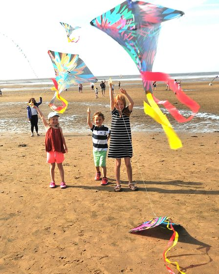Bea, aged five, Monty, aged four, and Thea, aged eight, flying kites. Picture: Jeremy Long