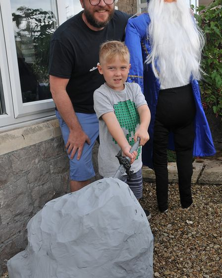 Freddy Penrose 7 tries to pull the sword from teh stone with his dad Benjamin with their scarecrowUp