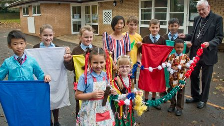 St Francis Primary School pupils in national costumes and holding a giant rosesary as part of their