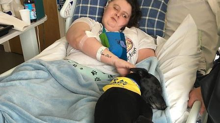 Tara in hospital with her support dog Flash.