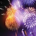 Firework rockets flying into the air and bursting into gold orange and purple breaks lighting up the