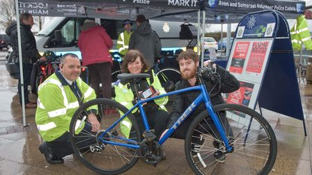 Mercury reporter Henry Woodsford having his bicycle security marked by PCSO's Kayley and James.