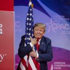 U.S. President Donald Trump hugs the U.S. flag