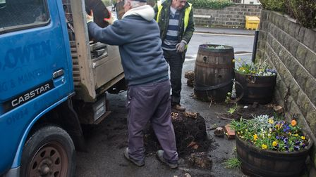 Volunteers clearing up the mess left by vandals knocking over Hutton in Bloom planters. Picture: