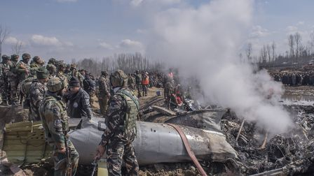 Indian forces attend the scene of a crashed Indian Air Force aircraft which killed six people after