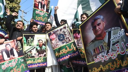 Pakistani traders shout slogans and carry posters with the image of Pakistani Army Chief General Qam