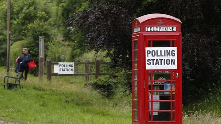 A polling station sign is seen on a telephone box outside the polling station. Photo: ADRIAN DENNIS/