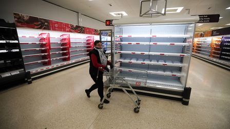 People shop as empty shelves are seen in Sainsbury's. Picture: Nick Potts/PA Wire