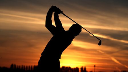 A golfer drives off into the sunset