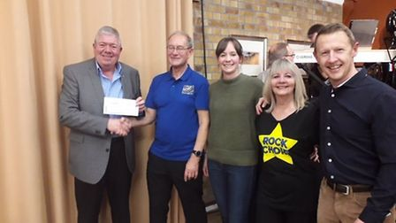 Steve Chapman handing the money over to Mike and Jill Pope and Sam and Andy Brindle.