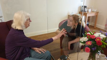 The care home has installed an airtight partition to enable loved ones to meet.