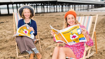 Anna Farthing and Fiona Matthews reading Boredom Busters newspaper on Weston Beach. Picture: Paul Bl