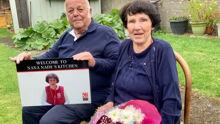 Nadine and Tony Garbett in their garden with the sign that will take pride of place at Nana Nade's k