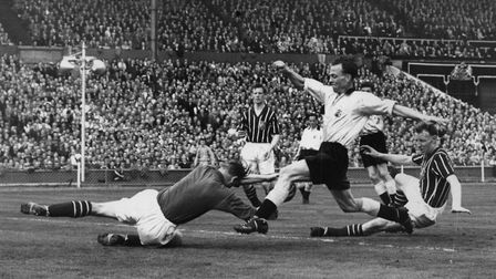 Manchester's goalkeeper Bert Trautmann dives at the feet of Birmingham's Murphy during the match. It