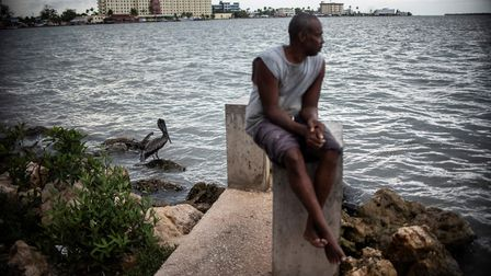 A man sits on a pier in Belize City. Picture:PEDRO PARDO/AFP/Getty Images