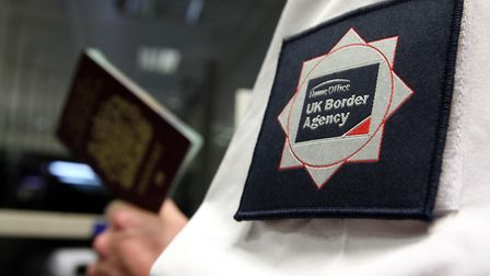 UK Border Agency officer checking a passport in the North Terminal of Gatwick Airport, Sussex. Photo