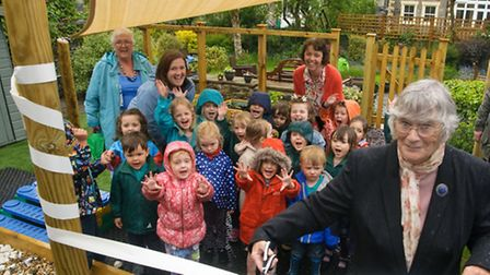 Ribbon being cut by Gina Connolly, widow of John Connolly who cared for the garden at the school for