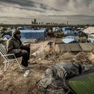 """A Sudanese man looks on as he uses a phone to call his family in the """"Jungle"""" migrants camp in Calais"""