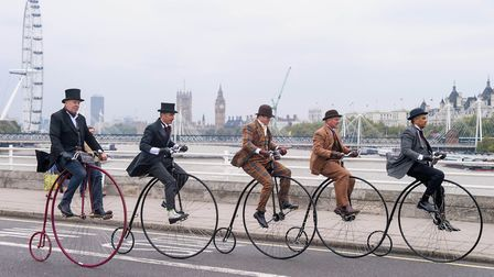 Penny-farthing bicycles are ridden across Waterloo Bridge in London. Photograph: Anthony Upton/PA.