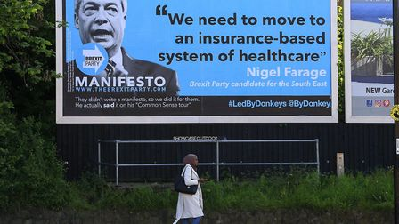 A woman walks past a billboard aimed at The Brexit Party leader Nigel Farage. Picture: Led By Donkey