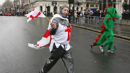 A man dressed as Saint George crosses the road beside a man dressed as a dragon outside the Houses o